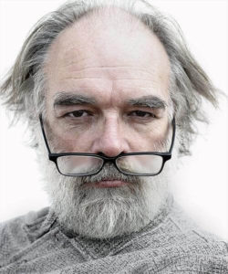 Old man with gray hair and beard wearing reading glasses
