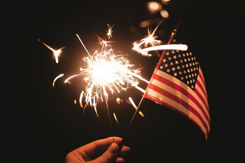 hand holding sparkler and mini flag of the US