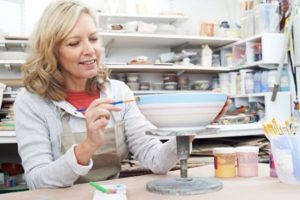 middle-aged woman painting a ceramic bowl