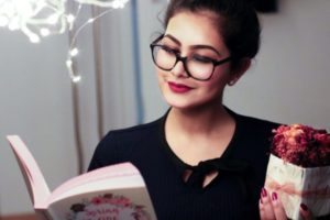 young woman with reading glasses and a book
