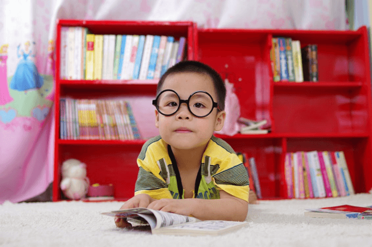 child wearing glasses reading a comic book